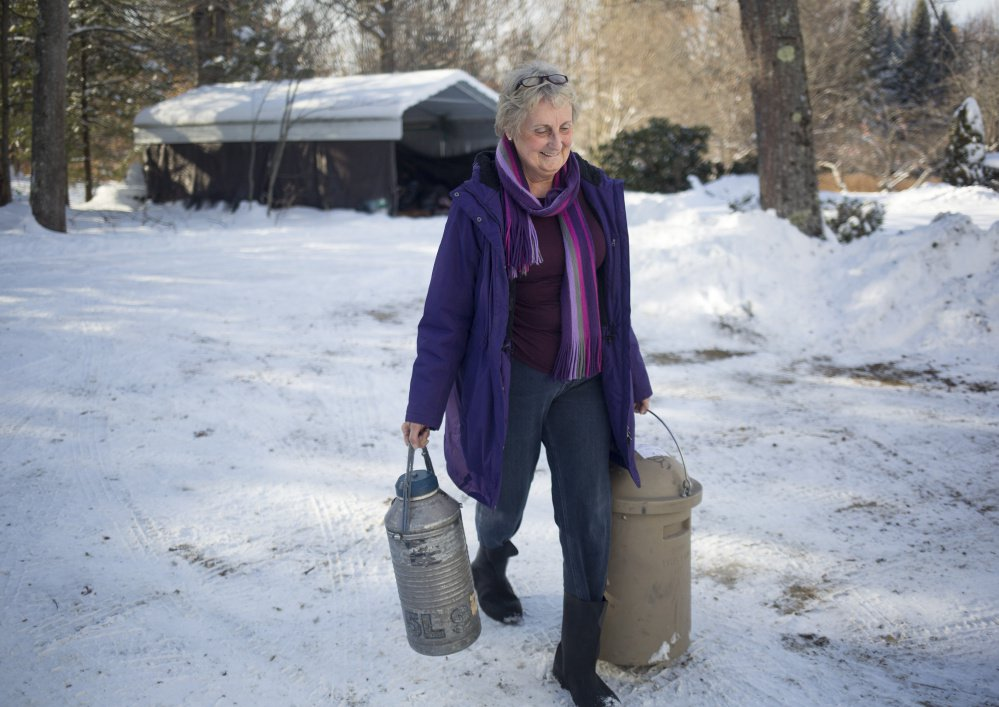 Carolyn Woerter carries containers for her bull semen business to her truck in Freeport. She takes the product all around the state, for both dairy cow and beef breeding.