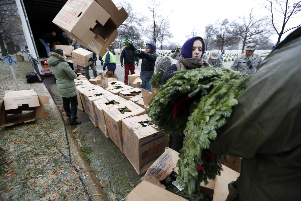 Volunteer Alyssa Kane of Alexandria, Va., passes out wreaths to be placed at graves as part of Wreaths Across America at Arlington National Cemetery, Saturday, Dec. 17, 2016 in Arlington, Va. Organizers estimate more than 245,000 wreaths were placed at graves throughout the cemetery. (AP Photo/Alex Brandon)