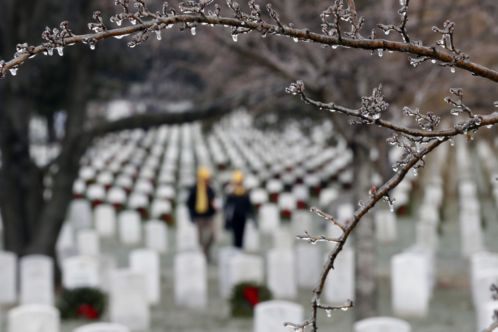 Ice is seen on trees as volunteers place wreaths at graves during Wreaths Across America at Arlington National Cemetery, Saturday, Dec. 17, 2016 in Arlington, Va. Organizers estimate more than 245,000 wreaths were placed at graves throughout the cemetery. (AP Photo/Alex Brandon)