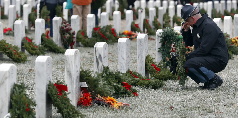 Maine State Police Detective Chad Lindsey pauses at a friend's grave in Section 60 as he carries a wreath to be placed at another grave, during Wreaths Across America at Arlington National Cemetery, Saturday, Dec. 17, 2016 in Arlington, Va. Organizers estimate more than 245,000 wreaths were placed at graves throughout the cemetery. (AP Photo/Alex Brandon)