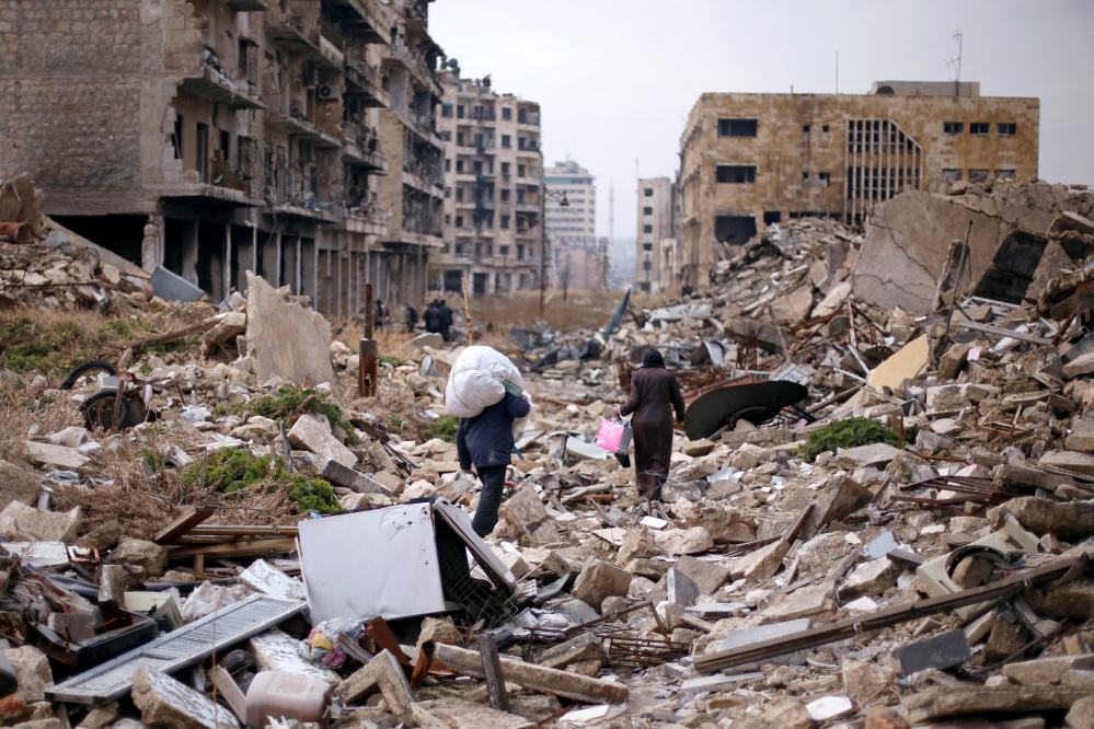 People walk amid the rubble as they carry belongings that they collected from their houses in the government controlled area of Aleppo, Syria, on Saturday.