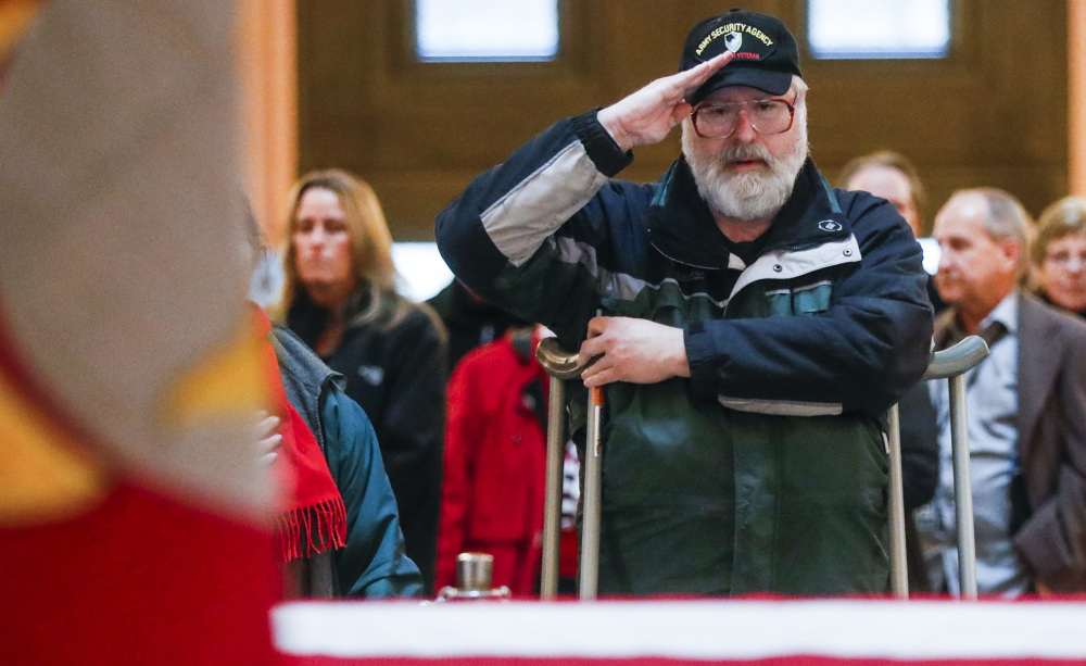 A mourner salutes the casket of John Glenn as he lies in state Friday in Columbus, Ohio. The former fighter pilot, astronaut and Democratic senator died Dec. 8 at 95.