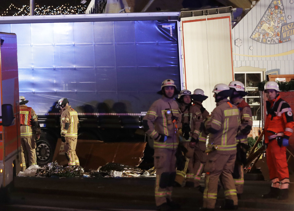 Firefighters stand beside the truck that ran into a crowded Christmas market, killing and injuring multiple people in Berlin, Germany, on Monday.