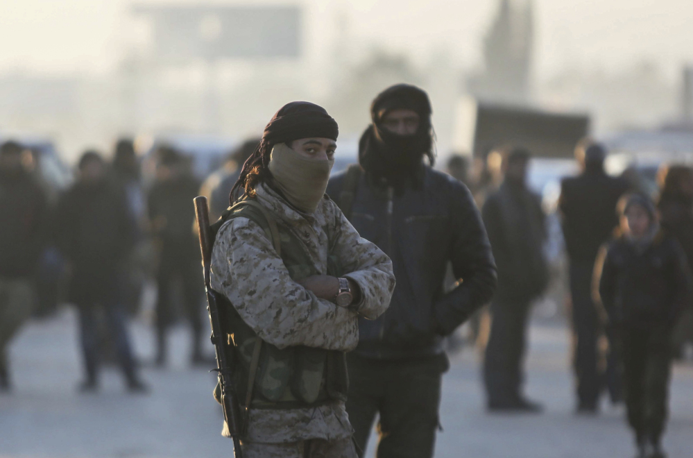Armed Syrian fighters evacuated from the embattled Syrian city of Aleppo during the ceasefire arrive at a refugee camp in Rashidin, near Idlib, Syria, on Tuesday. The Syrian army said Thursday that it has taken control of the city, which has been in rebel hands.