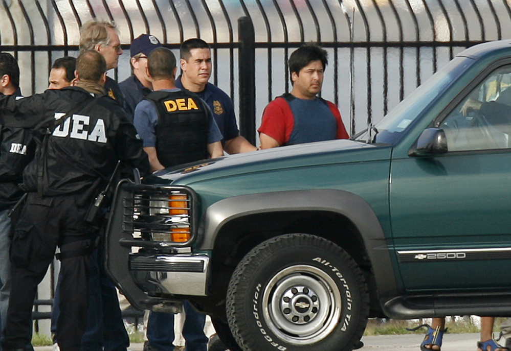 Drug Enforcement Agency personnel arrest a suspect in San Diego, Calif. As the agency has expanded enforcement to address the nation's opioid epidemic, drug companies have been hiring away former top-level DEA officials for their expertise.