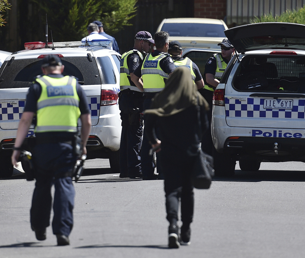 Police accompany a woman at the scene where a house was raided at Meadow Heights in Melbourne, Australia on Friday. Police in Australia detained five suspects who were allegedly planning a series of Christmas Day bomb attacks.