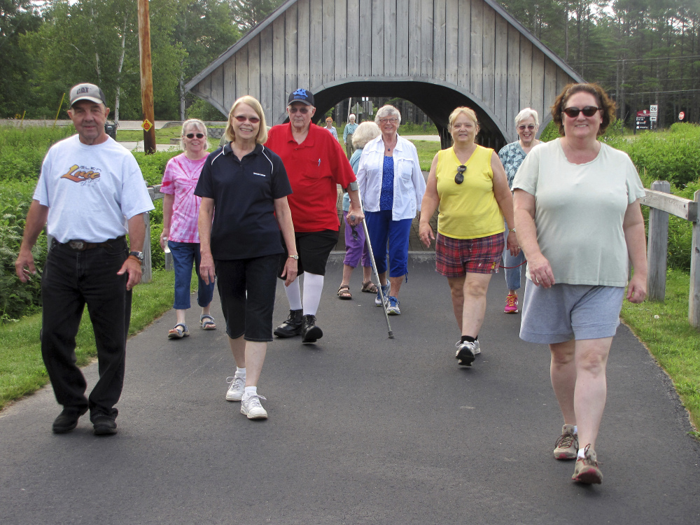 A group walks along a paved pathway in Bethel, Maine, and includes John Holliday, fourth from left wearing a red shirt.