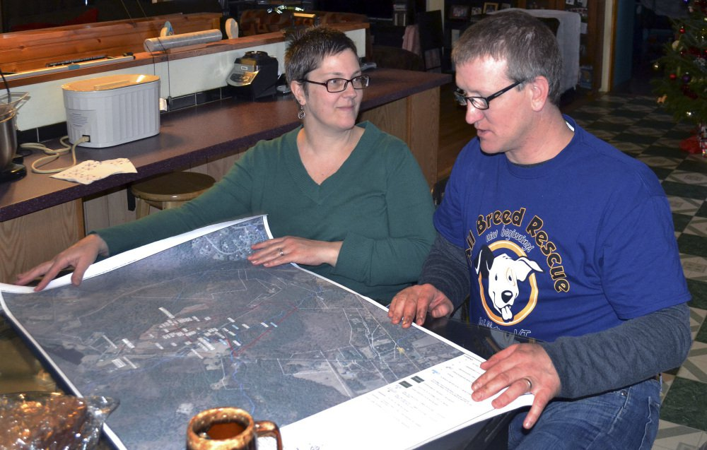 Debbie and Richard Higgins, whose well water has been contaminated by a suspected carcinogen from a Dartmouth College dump site, look at a map on their kitchen table in Hanover, N.H., which shows where the contamination has spread. Dartmouth says it has spent around $8.4 million cleaning up contamination where scientists dumped carcasses of lab animals in the 1960s and 1970s.