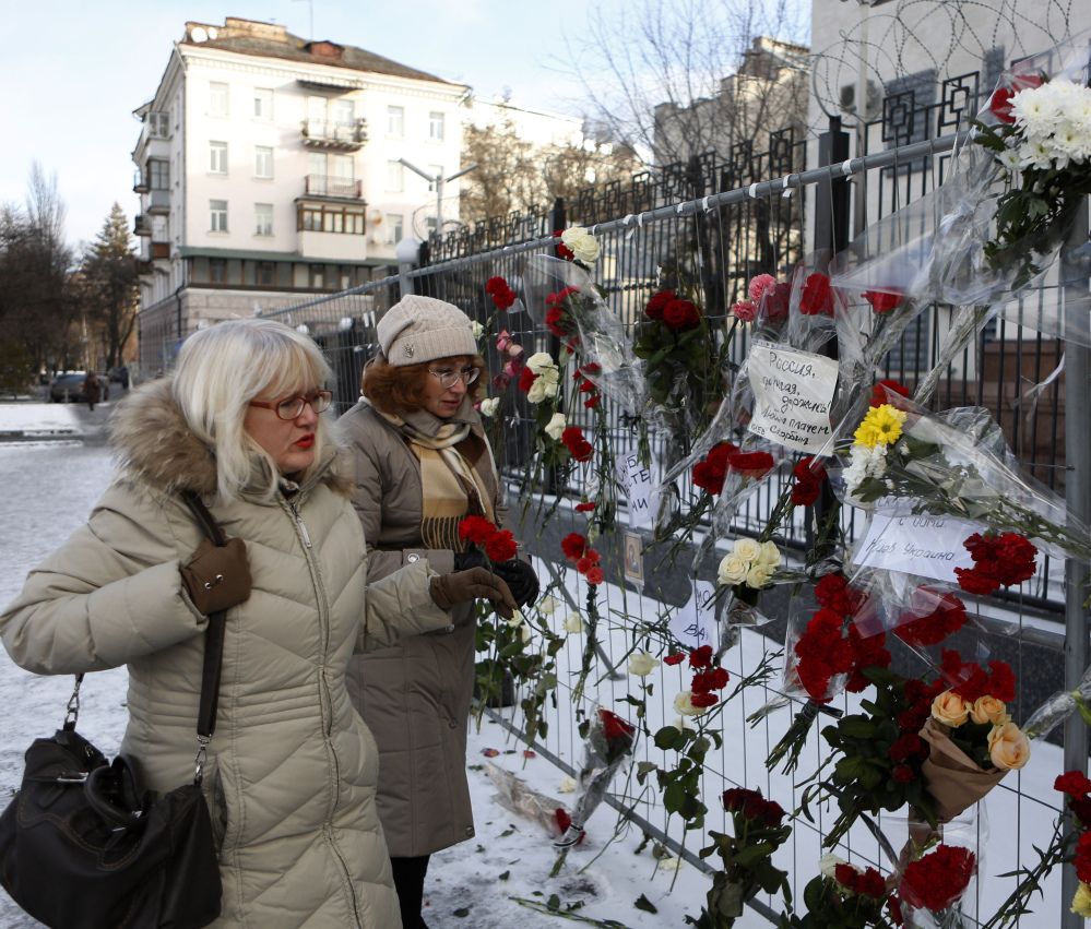 Women put flowers in front of the Russian embassy in Kiev, Ukraine, on Monday in memory of the passengers and crew who died in the crash of a military jet.
