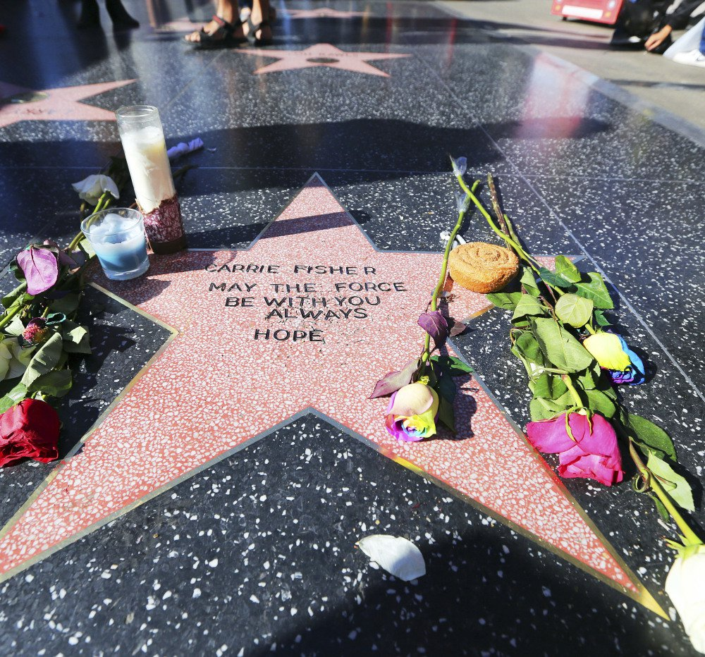 """Flowers, candles and the phrase """"May the force be with you always"""" adorn an impromptu memorial to Carrie Fisher in Hollywood."""