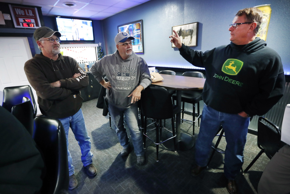 "Ron Oberhelman, right, talks with Rod Nelson, left, and Jeff Thompson in their Blue Moose Saloon, which opened in September in Renwick, Iowa. Oberhelman, a 59-year-old farmer who has seen the population fall from about 500 to 235 residents says, ""It's not our hometown. When your local place closes up, you're pretty much lost."""