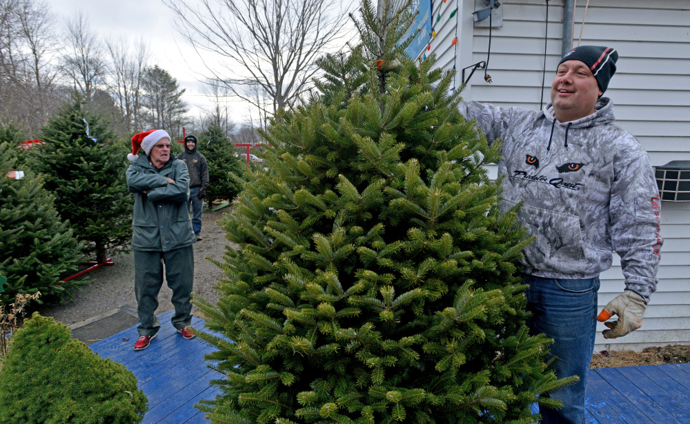Scott Knight stands with his new Christmas tree Saturday as Bryant LaPlante, owner of The Forest, a Christmas tree farm in Cornville, stands in the back.