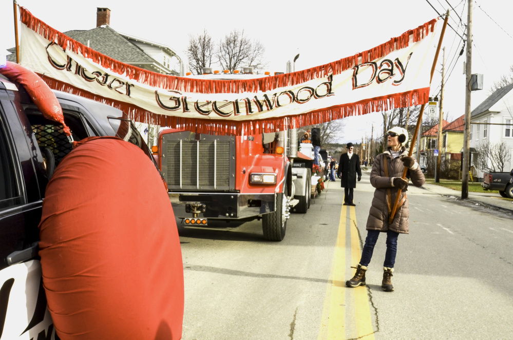 A woman readies a banner Saturday in Farmington as the 40th Chester Greenwood gets underway, honoring the inventor of earmuffs. In back, donning a black coat, hat and the trademark earmuffs, is Clyde Ross, who portrays Greenwood every year during the parade.