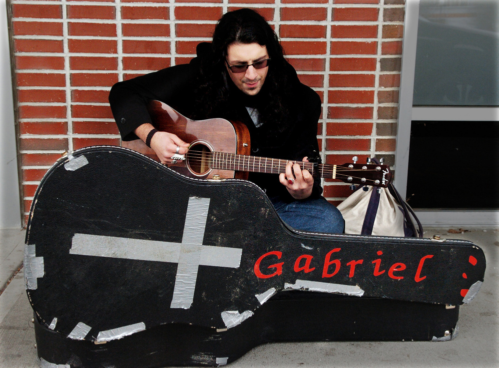 Michael Pastore sings and plays his guitar he calls Gabriel on the sidewalk outside of the Chapter 11 store in Waterville on a cold Wednesday.