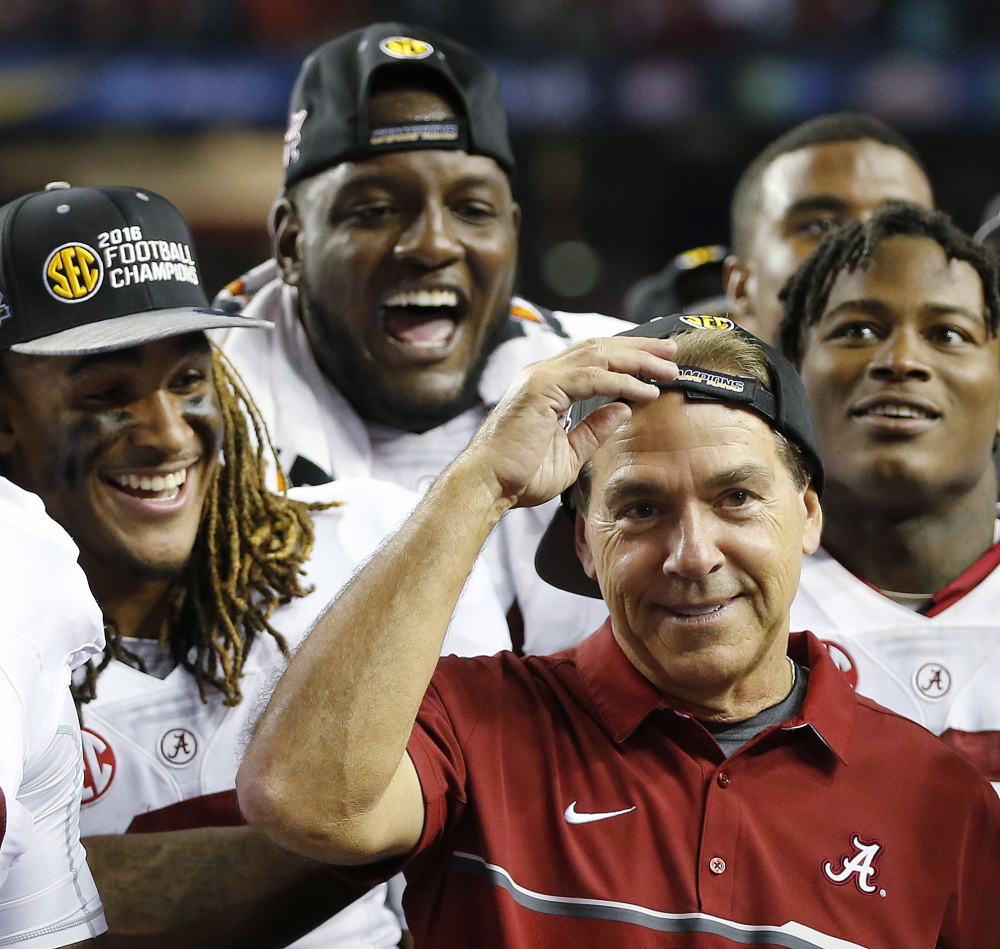 Alabama head coach Nick Saban and team members celebrate after the Southeastern Conference championship game against Florida on Saturday in Atlanta. Alabama won 54-16 and will be the No. 1 seed in this year's College Football playoffs.