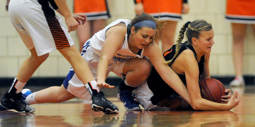 Madison's Marah Hall, left, battles for a loose ball with Skowhegan's Sydney Reed during the second annual Amanda Berry Scholarship game on Tuesday night in Skowhegan.