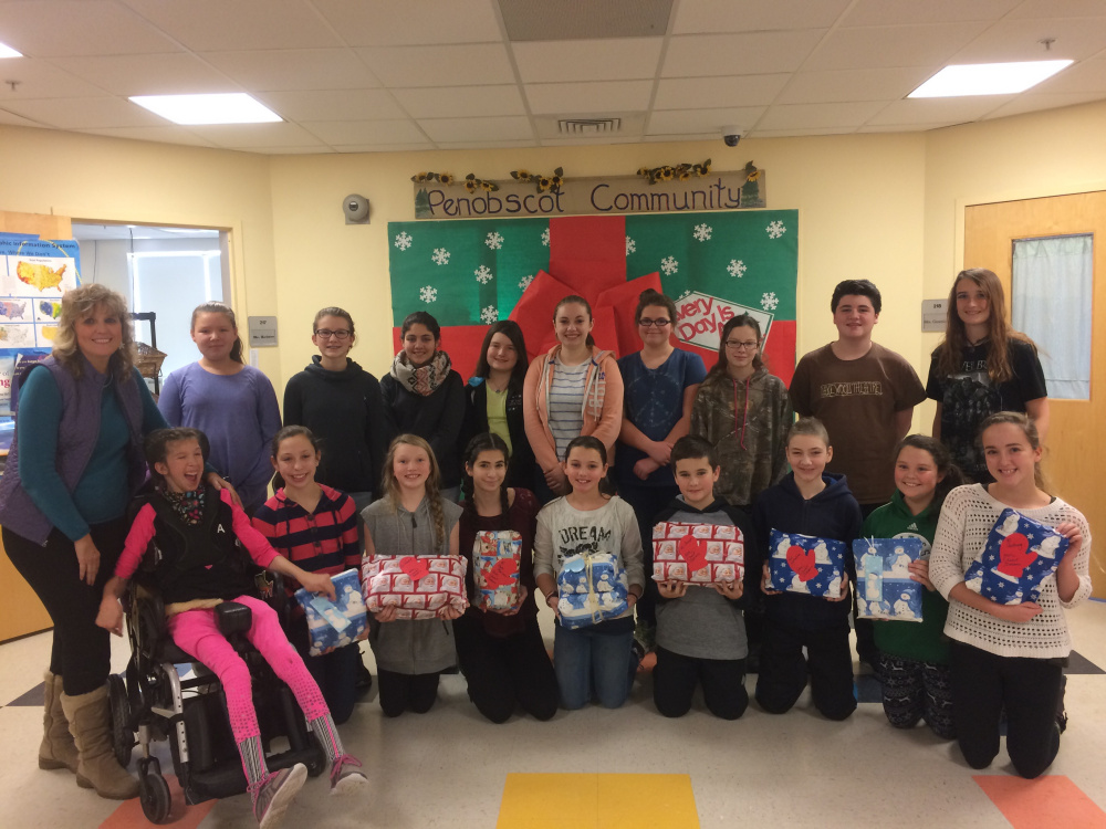 Deb Tanner, Somerset County's Teacher of the Year for 2015, left, worked with members of the Skowhegan Area Middle School student council to wrap gifts of pajamas and books for area children for Christmas as part of Tanner's Sweet Dreams Project to fight poverty.