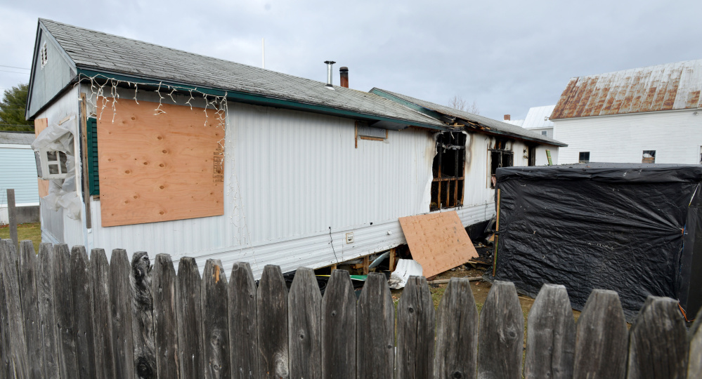The rear side of a mobile home on North Avenue in Skowhegan is seen Saturday after having caught fire the previous night, injuring a child and mother.