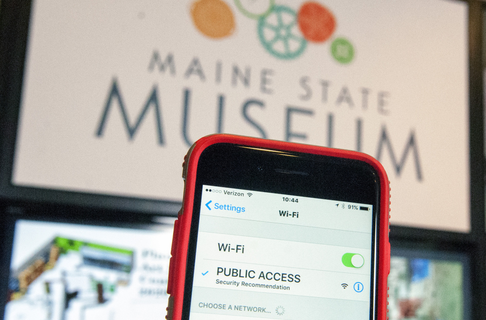 A smartphone's detection of a new Public Access Wi-Fi network is seen in front of a new display Thursday at the Maine State Museum in Augusta.