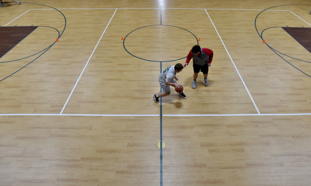 Members of the Temple Academy boys basketball team practice on its new hardcourt Thursday.