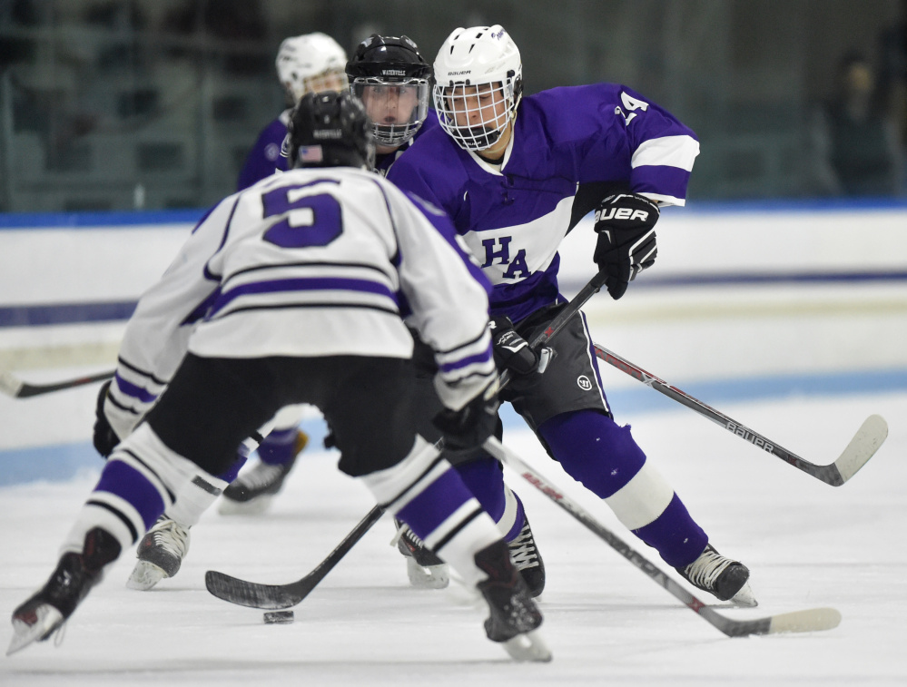 Waterville Senior High School's Andrew Roderigue (5) defends Hampden Academy's Joey McLain in the first period at Alfond Rink on Saturday night.