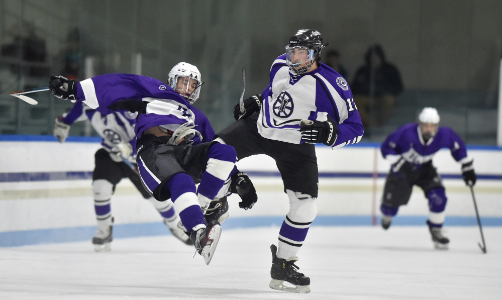 Waterville Senior High School's Zach Smith, right, knocks Hampden Academy's Marcus Dunn to the ice in the first period Saturday night at Colby College's Alfond Rink.