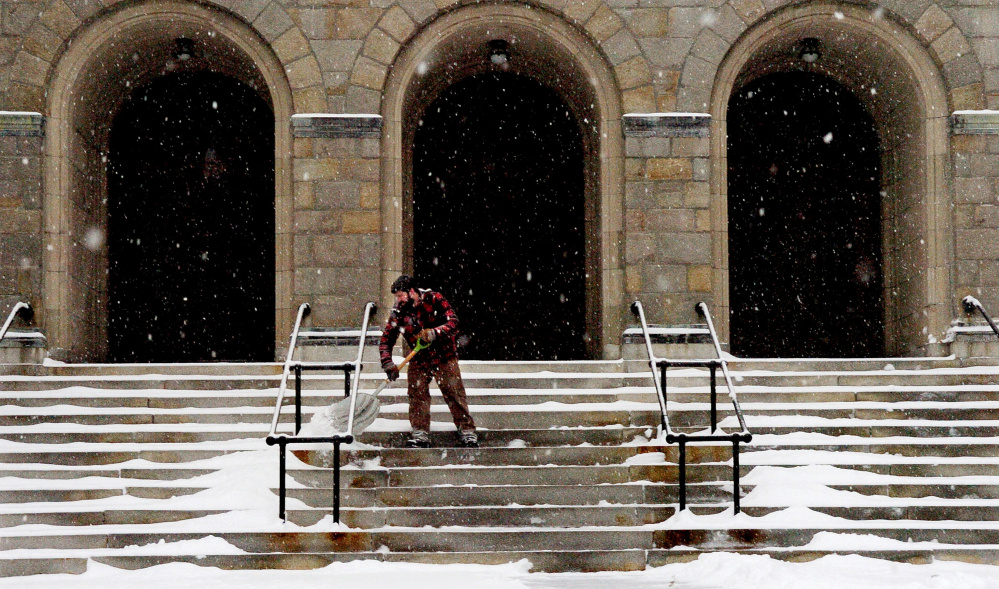 Sean Lawrence shovels snow from the steps leading into the Sacred Heart Church in Waterville on Monday.