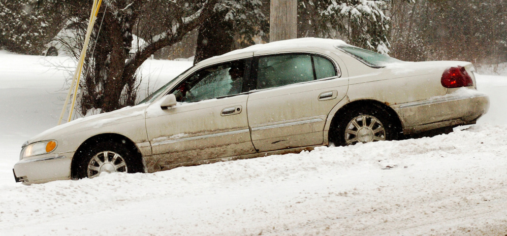 A driver waits in his car for a wrecker after sliding off the snow-covered Cushman Road in Winslow and coming to a stop against a utility pole on Monday.