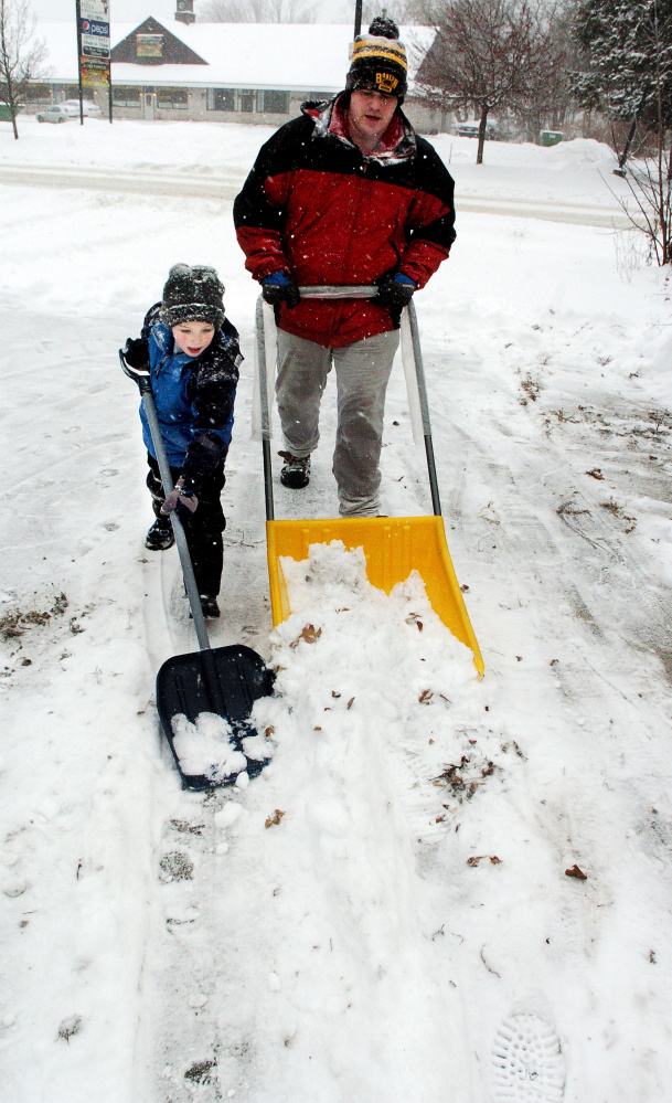 Korvyn Veilleux and his stepfather Edward Hoyt worked together to clear snow from a driveway in Fairfield on Monday.