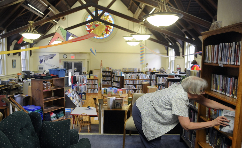 Gardiner Public Library teenage librarian Ginni Nichols sorts books in the children's reading room in this September 2015 file photo.