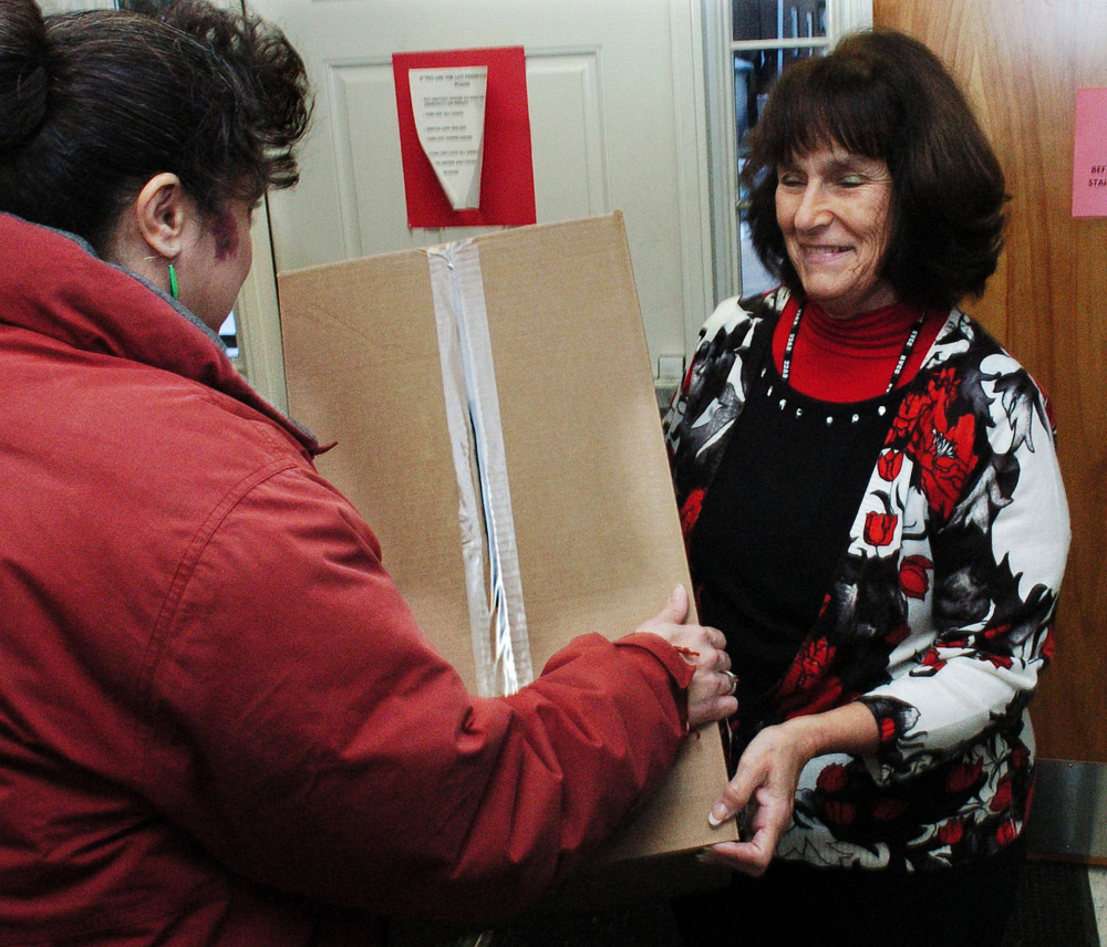 Volunteer Debbie Plummer, right, hands a box with children's gifts and clothes to a recipient who asked not to be identified by name at the Maine Children's Home for Little Wanderers in Waterville on Tuesday.