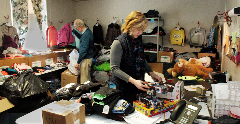 "At the Maine Children's Home for Little Wanderers in Waterville, Director of Development Steve Mayberry and Christmas Program Director Cristen Sawyer sort through kids toys and clothing on Tuesday. ""We have had an awesome response of donations of clothes, toys and money from really generous people,"" Sawyer said. Mayberry added that 1,759 kids will receive gifts this year."