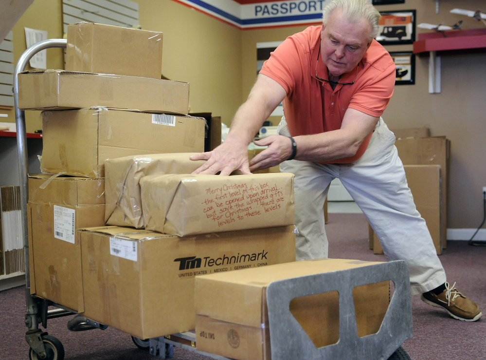 Keith McCray stacks packages to ship Wednesday at the Mailing Center in Augusta.