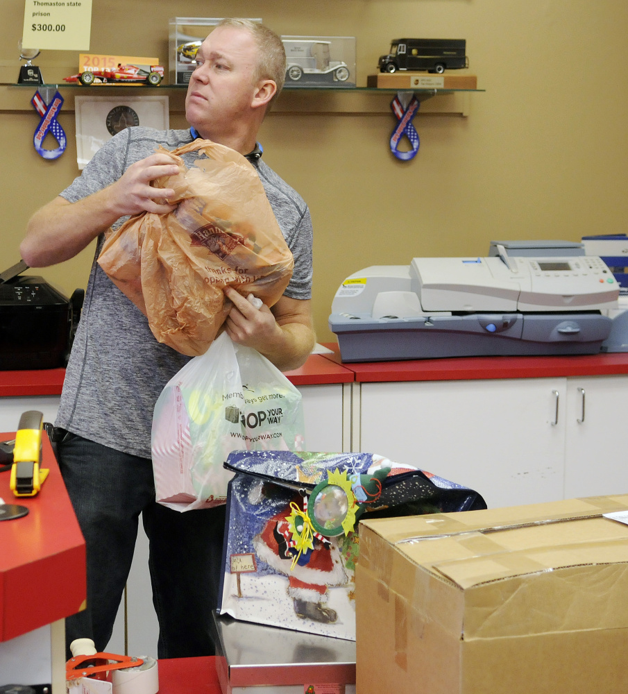 Kris McCray collects packages to ship Wednesday at the Mailing Center in Augusta.