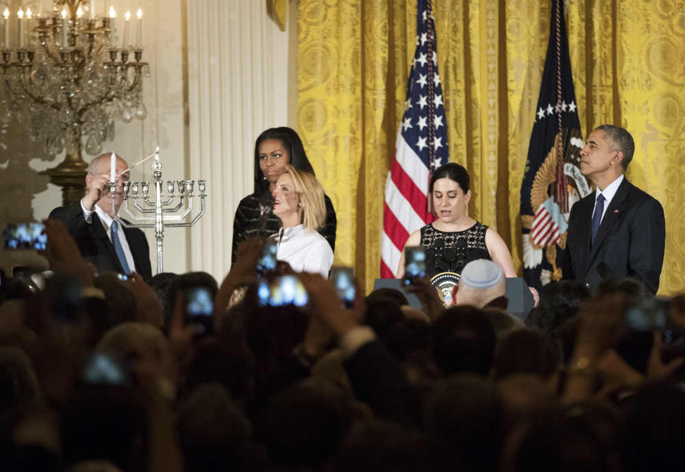 Rachel Isaacs, second from right, rabbi at Colby College and of Beth Israel Congregation in Waterville, gave the invocation at Wednesday night's White House Hanukkah reception. With the invocation over, Chemi Peres, left, and Mika Almog, at left and second from left in front, son and granddaughter of former President of Israel Shimon Peres, light the Menorah while first lady Michelle Obama, behind Almog, and President Barack Obama, right, watch during a reception in the East Room of the White House in Washington.