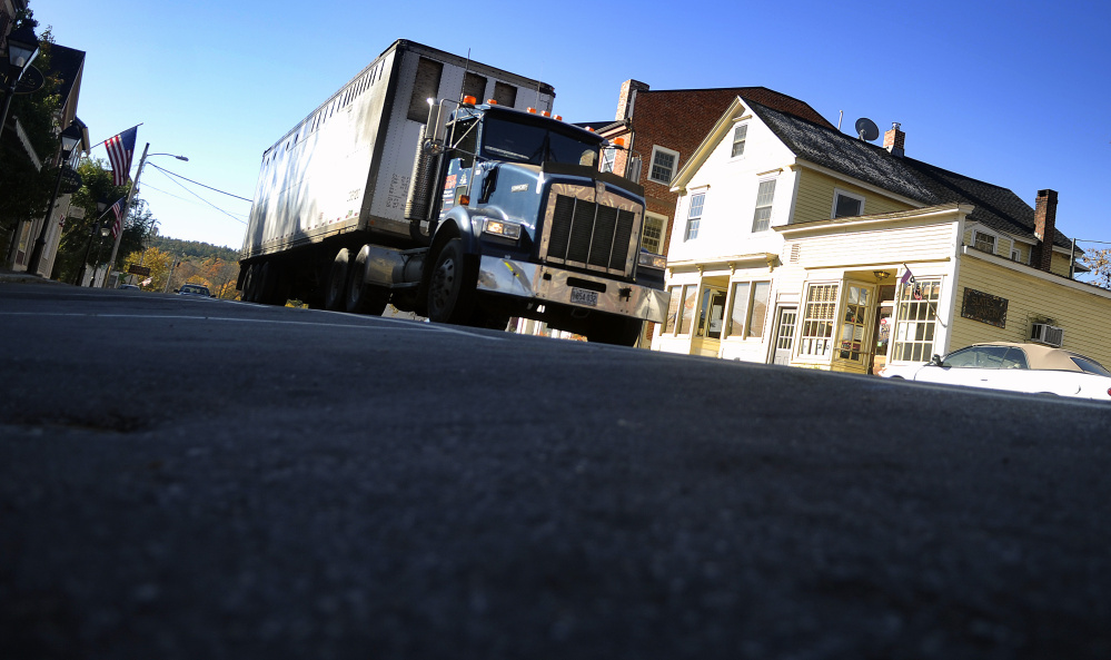 A truck moves in October 2015 along Water Street in Hallowell where the Maine Department of Transportation plans to reduce the crown in the road.
