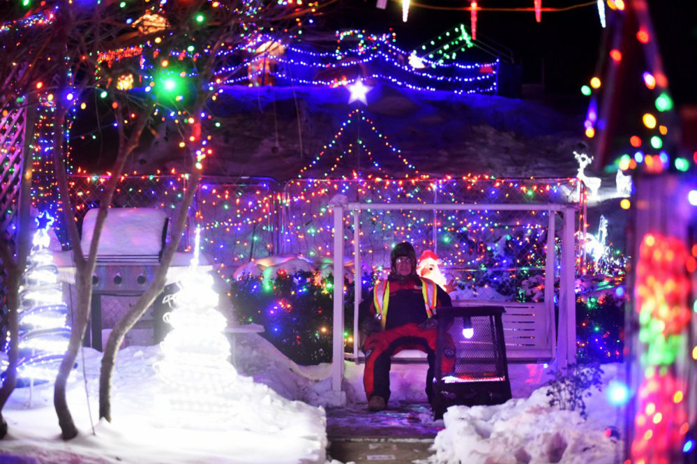 Donald Lagasse sits on Thursday among the many thousands of lights on display at his home, which is part of the China Road Christmas Park, on China Road in Winslow.
