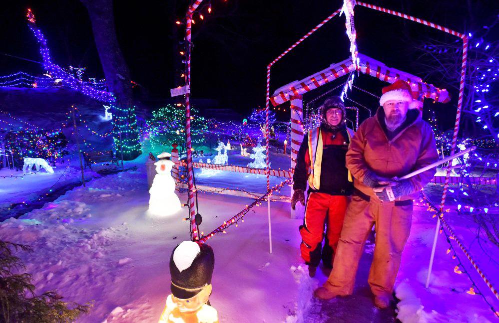 Donald Lagasse, back left, and Ric Spaulding, right, stand on Thursday among the many thousands of lights on display at their homes, also know as the China Road Christmas Park, on China Road in Winslow.