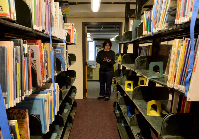 Tammy Rabideau, assistant director at the Waterville Public Library, stands among damaged books Saturday in the library's children's section in Waterville.