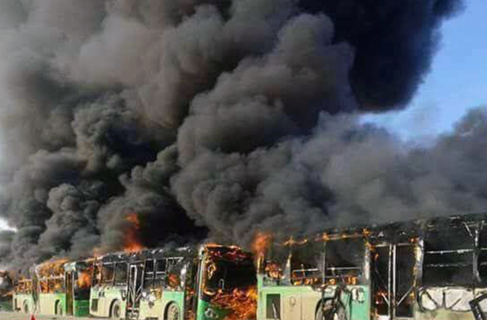 Smoke rises over burning government buses in Syria on Sunday. Activists said militants have burned at least five buses assigned to evacuate wounded and sick people.