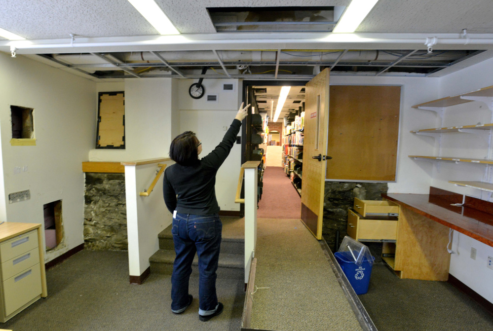 Tammy Rabideau, assistant director at the Waterville Public Library, points to the pipe that broke over night that damaged books and computers in Waterville on Saturday. The library continues cleanup on Monday.