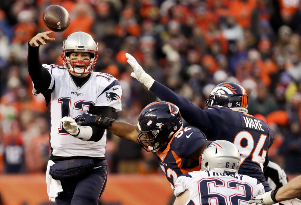 New England Patriots quarterback Tom Brady passes under pressure against the Denver Broncos during the second half Sunday, in Denver.