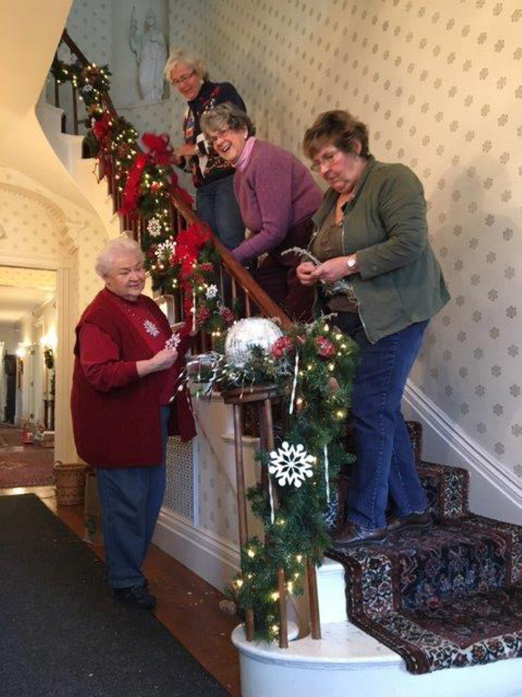 Kennebec Valley Garden Club members decorate the Blaine House stairway, front door entry and rooms in preparation for all the festivities during the holiday season. From top are Debbie Sherman, Joan Hague, Karen Foster and Jean Matheson.