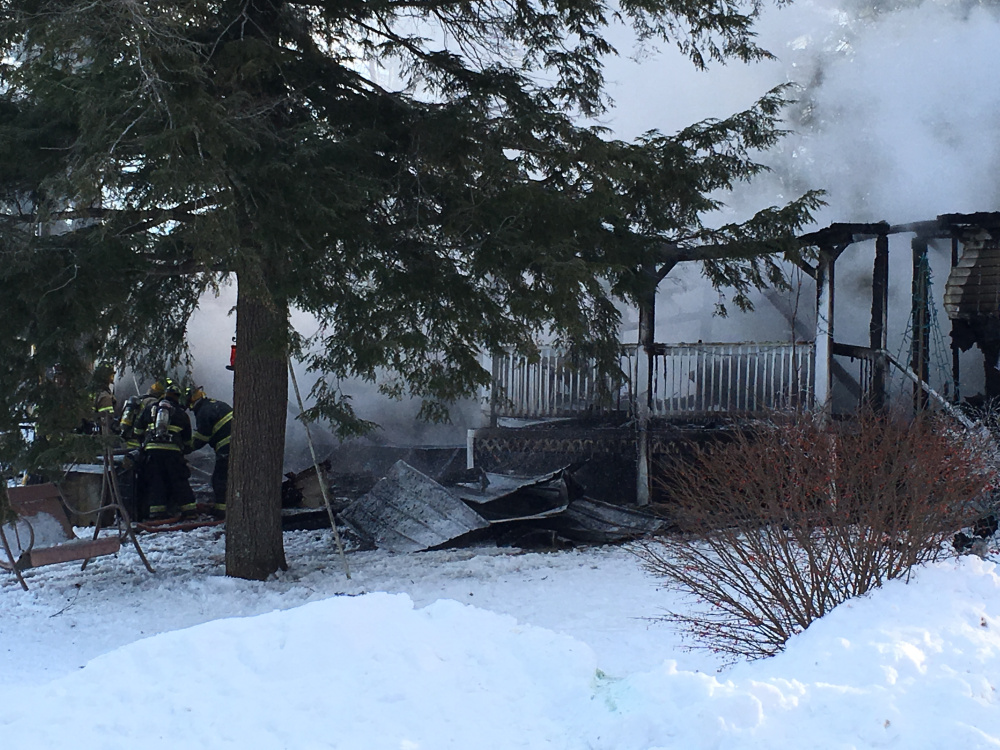 Firefighters continue to work in frigid weather Tuesday morning to put out a mobile home fire on Blue Rock Road in Monmouth.