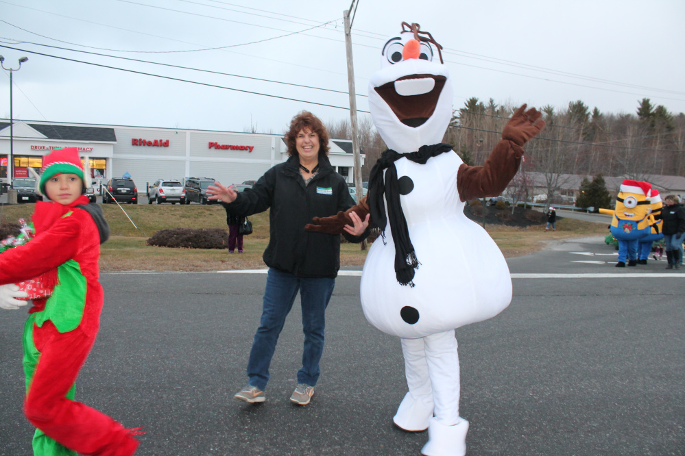 Winthrop Area Federal Credit Union employee Sandy Labreck escorts Olaf in the parade.