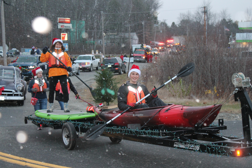 Tanner Webb, with Webb and Sons Paddling, paddles in his holiday float as his mother Laurie Webb stands on top of a paddle boat.