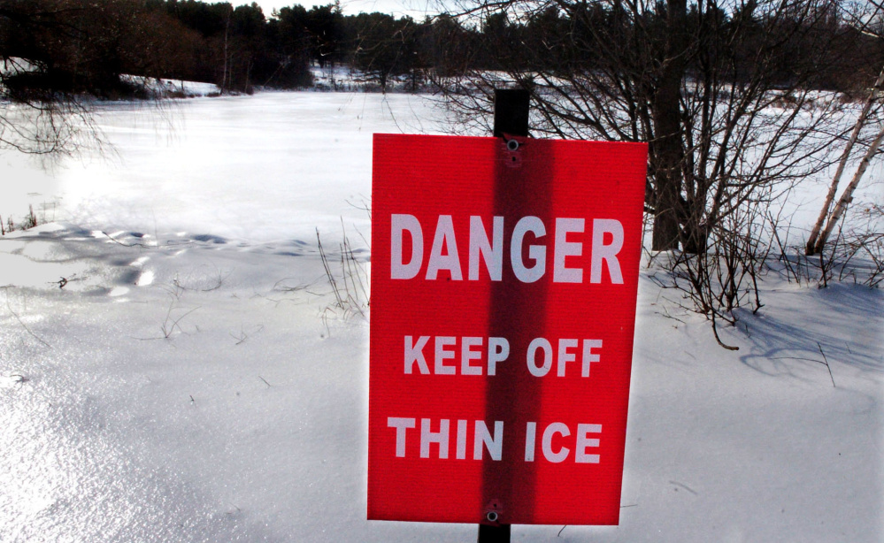 A sign standing Tuesday on the shore of Johnson Pond in Waterville warns skaters to stay off the ice, which might not be thick enough despite the recent cold weather. The Maine Warden Service also is warning fishermen to be cautious.