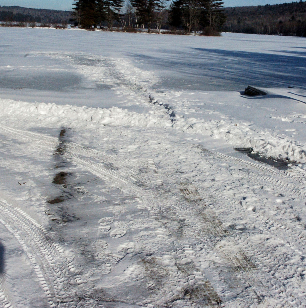 A boat landing on Tuesday shows evidence that a crew has plowed a path through the snow and onto the ice at Lake George Regional Park East in Skowhegan. The Maine Warden Service is warning ice fishermen and skaters to be wary of thin ice this early in the winter.