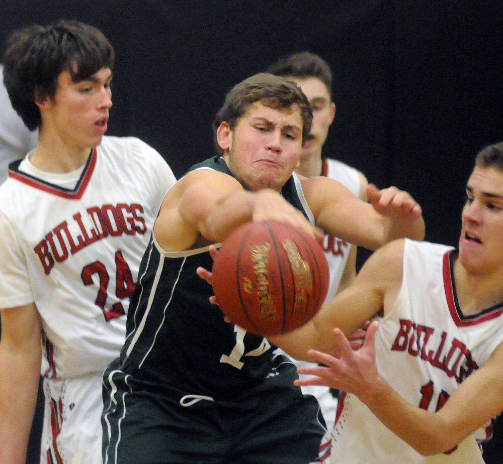 Hall-Dale's Alec Byron, right, and Owen Dupont (24) sandwich Carrabec's Dylan Willette during a Mountain Valley Conference game Tuesday in Farmingdale.
