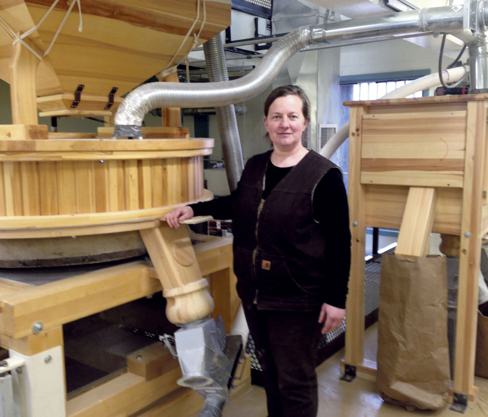 Amber Lambke stands beside a working mill while grinding flour in 2014 at the Somerset Grist Mill in Skowhegan. Lambke is president of Maine Grains.